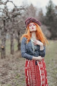 Stravagante giovane donna dai capelli rossi che indossa gioielli etnici, vestiti e turbante con un trucco insolito che balla o posa in una foresta o in un parco mistico. musica trance psichedelica, voodoo, concetto esoterico