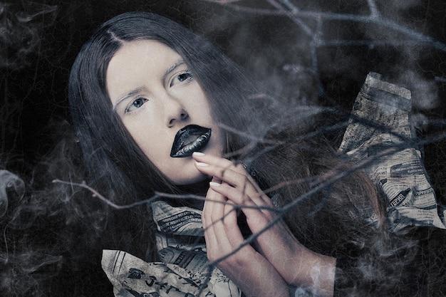 Donna stravagante con notizie di carta vestito. viso creativo, lato oscuro.