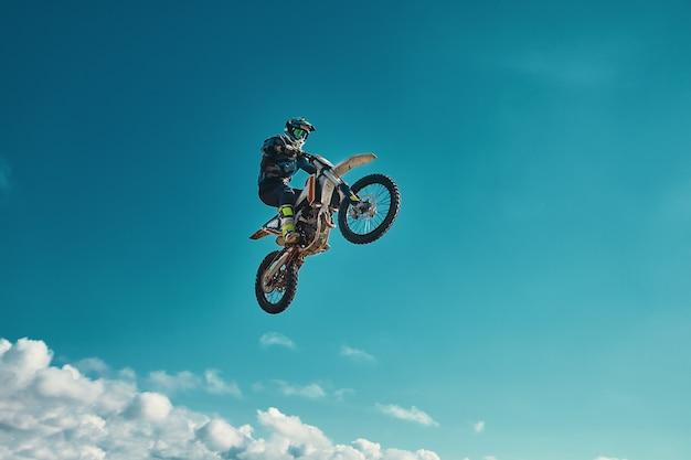 Concetto estremo, sfida te stesso. salto estremo su una moto su uno sfondo di cielo azzurro con nuvole.