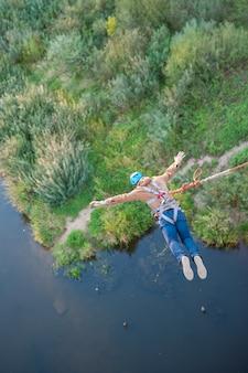 Salto estremo dal ponte. l'uomo salta sorprendentemente rapidamente nel bungee jumping allo sky park esplora il divertimento estremo. bungee nel canyon.