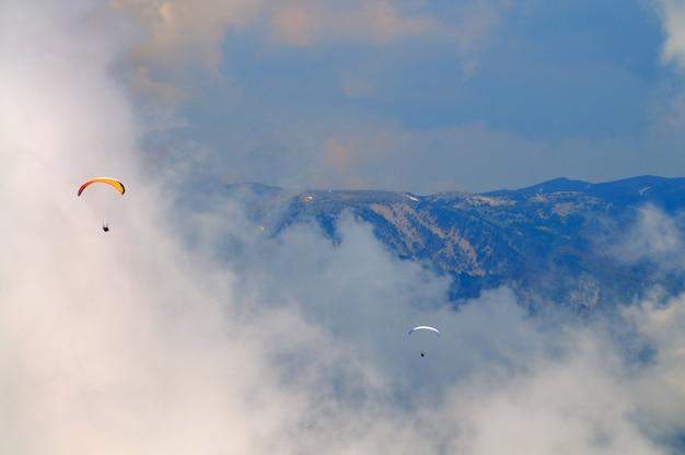 Ricreazione estrema, paracadutista vola sopra le montagne e le rocce. nuvole bianche in cielo