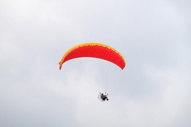Il pilota di sport estremi sta volando verso il cielo nuvoloso con un motore di paramotore