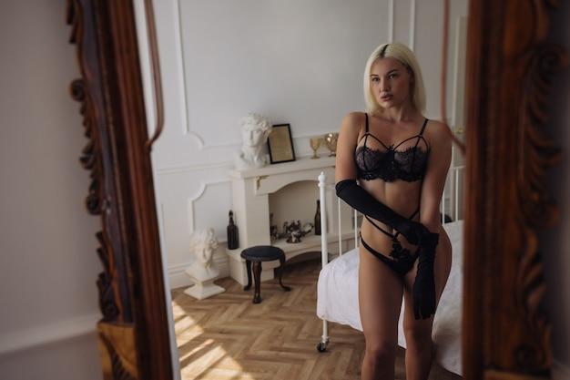 Estremamente bella e giovane donna caucasica adulta che indossa lingerie in una camera da letto boudoir in varie pose.