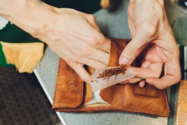 Vista estremamente ravvicinata delle mani di un uomo che mette un tabacco in una macchina del tabacco.