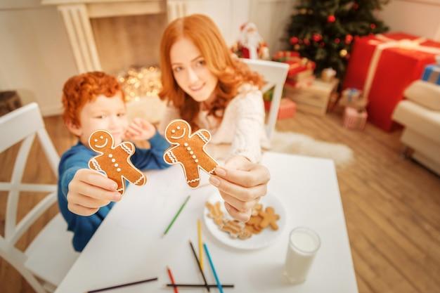 Estremamente delizioso. messa a fuoco selettiva su un paio di biscotti di pan di zenzero tenuti da una madre allegra e dal suo piccolo figlio seduti a un tavolo e disegnando.