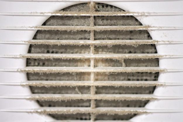 Griglia di ventilazione dell'aria estremamente sporca di hvac con filtro intasato polveroso, da vicino