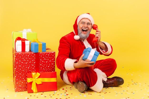 Uomo adulto estremamente eccitato che indossa il costume di babbo natale seduto vicino a molte scatole con regali di natale, parlando di saluto con le vacanze tramite telefono fisso, studio al coperto isolato su sfondo giallo