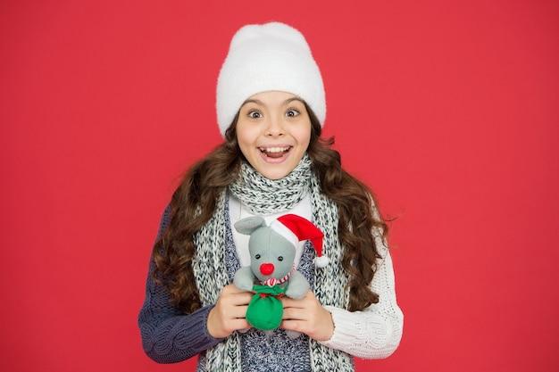 Una bambina estremamente felice con i capelli lunghi indossa abiti caldi e tiene in mano il giocattolo di natale presente dopo lo shopping, felicità.