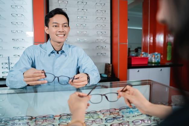 Un impiegato di una clinica oculistica sta servendo le consumatrici quando sceglie gli occhiali da utilizzare in una clinica oculistica