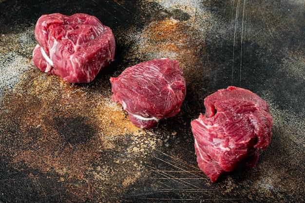 Set di bistecca di carne fresca marmorizzata di filetto di manzo occhio, sul vecchio rustico scuro