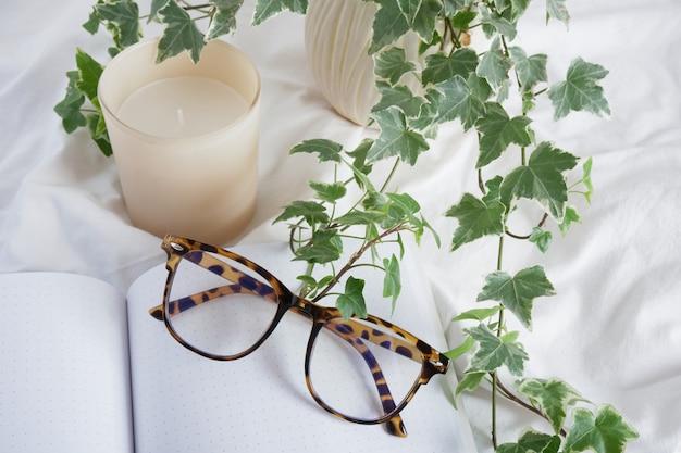 Occhiali da vista, candela aromatica, fiore in vaso e blocco note vuoto aperto su panno bianco stropicciato, pianificazione e lavoro a casa in uno spazio di copia confortevole