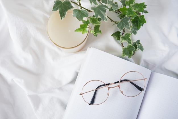 Occhiali da vista, candela aromatica, fiore in vaso e blocco note vuoto aperto su panno bianco stropicciato, pianificazione e lavoro a casa in tutta comodità