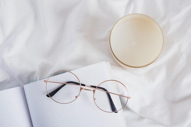 Occhiali da vista, candela aromatica e blocco note vuoto aperto su uno spazio di copia in tessuto bianco stropicciato