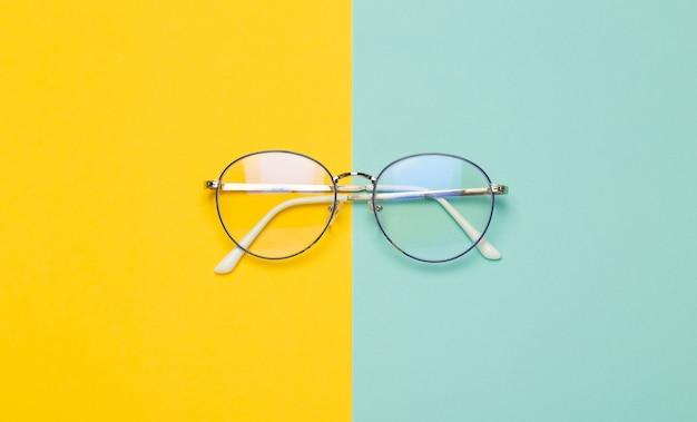 Occhiali da vista isolati sulla superficie gialla e blu.