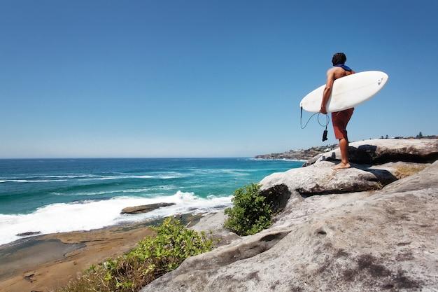 Inquadratura a livello degli occhi della schiena di un maschio che trasporta una tavola da surf in piedi su una roccia vicino al mare