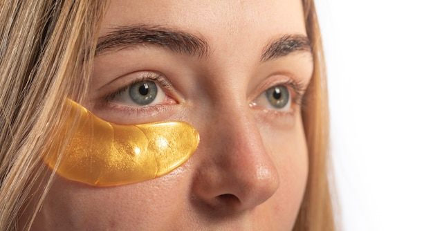 Benda sull'occhio sul viso di una giovane donna su sfondo chiaro.