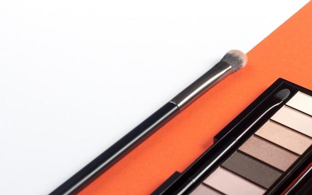 Tavolozza e spazzola dell'ombretto su fondo bianco ed arancio