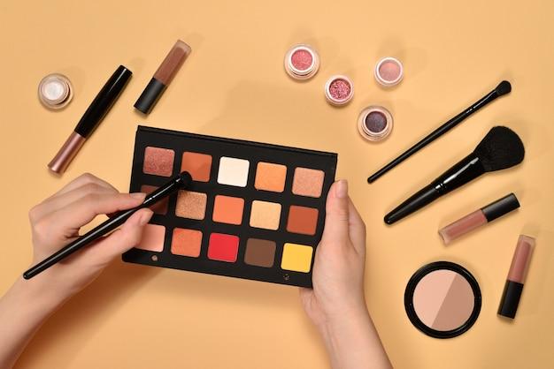 Tavolozza di ombretti sulla mano della donna. prodotti per il trucco professionale con prodotti cosmetici di bellezza, fondotinta, rossetto, ombretti, pennelli e strumenti.