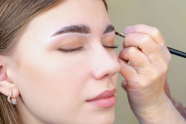 Colorazione delle sopracciglia. donna che applica la tinta della fronte con il primo piano della spazzola di trucco