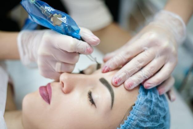 Microblading del sopracciglio. primo piano della signora che ha procedura di bellezza del viso in clinica moderna.