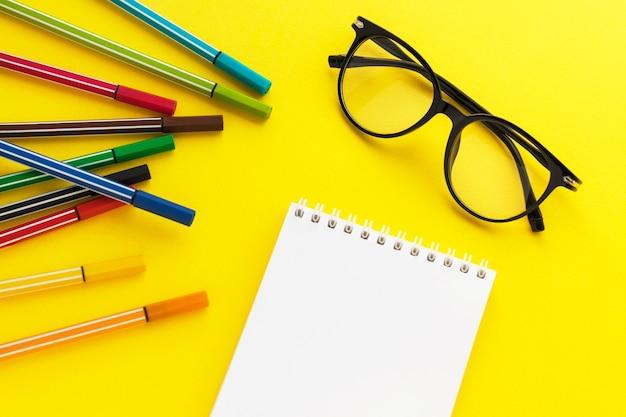 Occhiali da vista, blocco note vuoto e pennarelli colorati su sfondo giallo. pennarelli multicolori per il disegno del bambino.