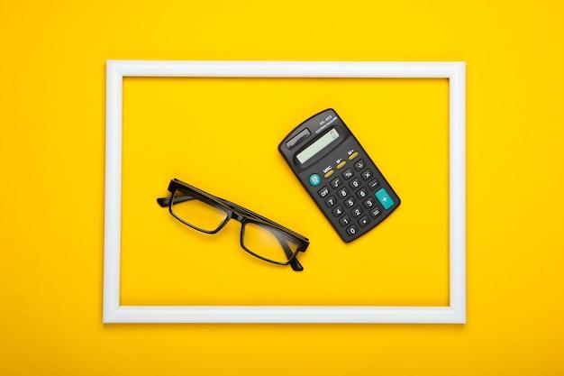 Occhiali da vista e calcolatrice in cornice bianca su superficie gialla