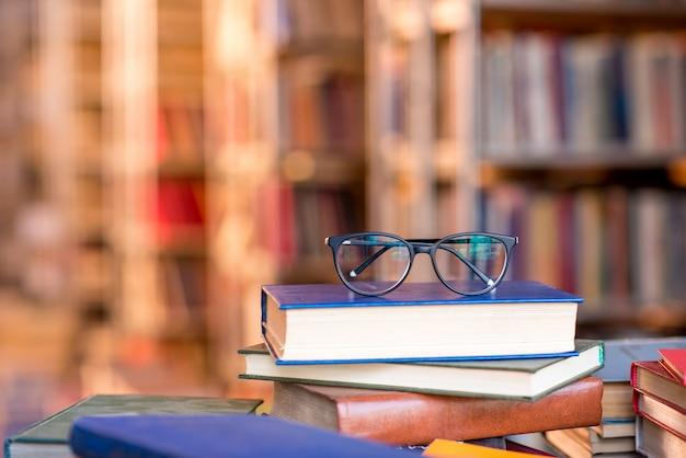 Occhiali da vista sdraiati sui libri in biblioteca. immagine con copia spazio