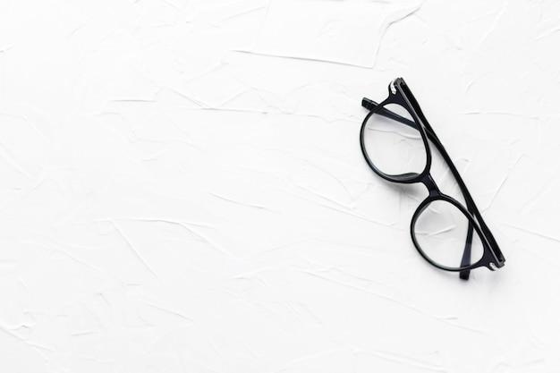 Occhiali da vista con montatura nera su sfondo bianco. occhiali da vista. occhiali rotondi con lenti trasparenti. primo piano occhiali da vista con tecnica sfocata. accessorio di moda. tema di oftalmologia. lay piatto.