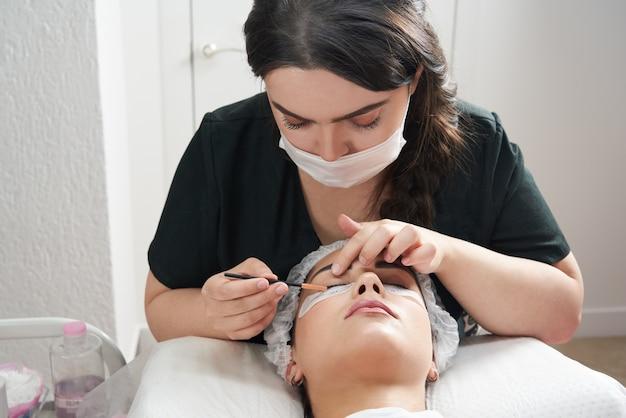 Procedura di estensione delle ciglia da vicino bella donna con ciglia lunghe in un salone di bellezza