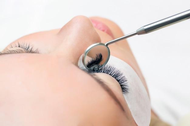Procedura di estensione delle ciglia occhio femminile con ciglia lunghe