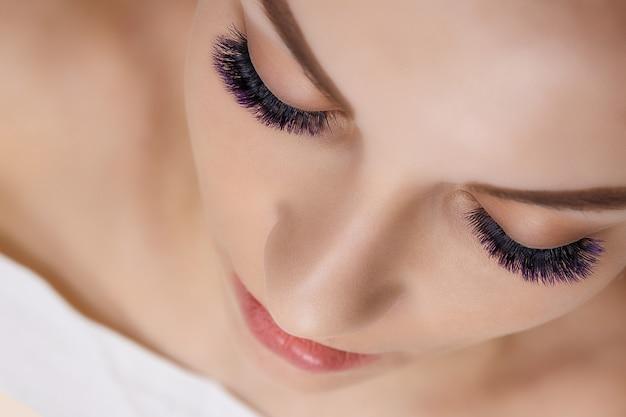 Procedura di estensione delle ciglia occhio donna con lunghe ciglia blu effetto ombre ravvicinata messa a fuoco selettiva