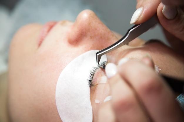 Procedura per l'estensione delle ciglia. occhio di donna con lunghe ciglia. ciglia, close up, macro, messa a fuoco selettiva.