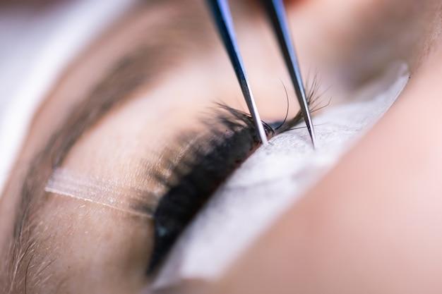 Procedura di estensione delle ciglia. occhio di donna con ciglia lunghe. ciglia, primi piani, macro, messa a fuoco selettiva
