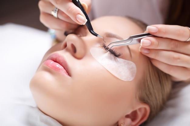 Procedura per l'estensione delle ciglia. occhio di donna con lunghe ciglia. ciglia, primi piani, messa a fuoco selezionata.