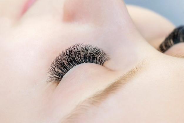 Extension per ciglia. primo piano degli occhi con ciglia estese e senza ciglia estese, ragazza bianca. prima e dopo