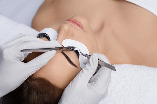 Estensioni delle ciglia, ciglia finte, procedura di estensione delle ciglia, master e cliente in un salone di bellezza,