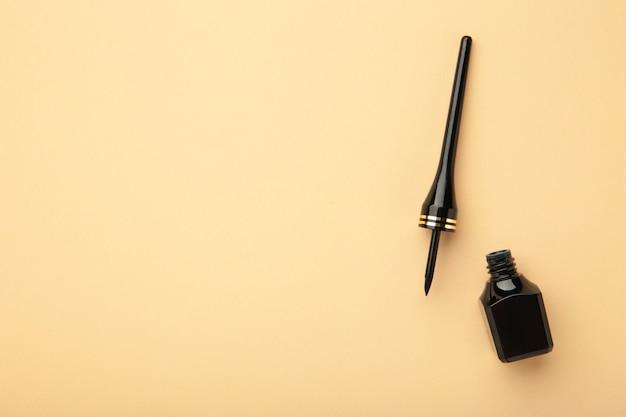Eyeliner su sfondo beige con copia spazio. vista dall'alto. concetto di bellezza