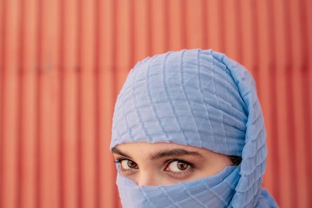 Occhi e sopracciglia di una bella giovane donna araba in hijab blu