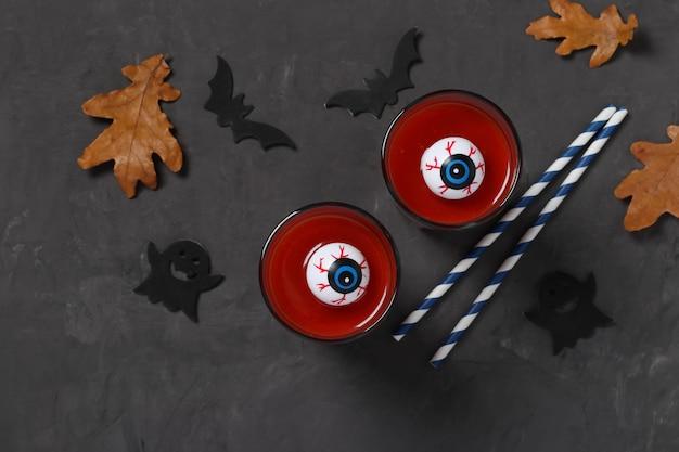 Occhi in vetro con cocktail di pomodoro sul tavolo scuro per le vacanze autunnali di halloween. vista dall'alto. disposizione piatta. formato orizzontale.