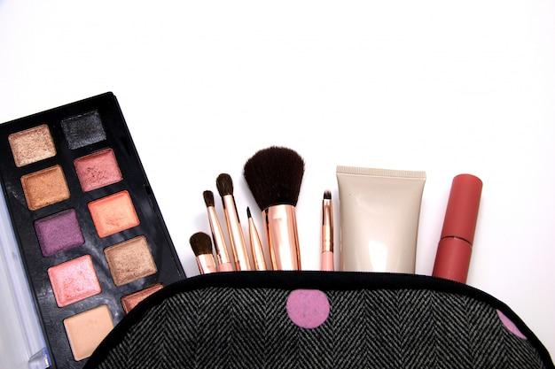 Eyes shadow in set cosmetici borsa di decorativi, strumenti di trucco su sfondo bianco.