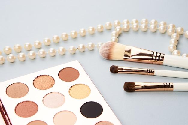 Ombretto trucco collezione di pennelli cosmetici professionali accessori perline su sfondo grigio