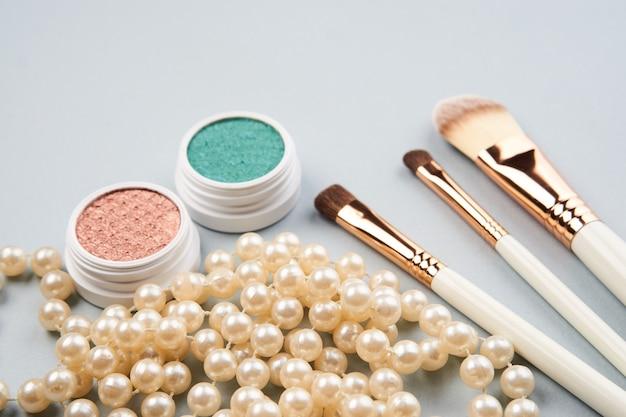 Ombretto trucco pennelli collezione cosmetici professionali accessori perline su grigio