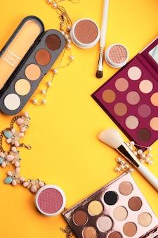 Ombretto cosmetici professionali cipria in polvere e sfondo giallo vista dall'alto