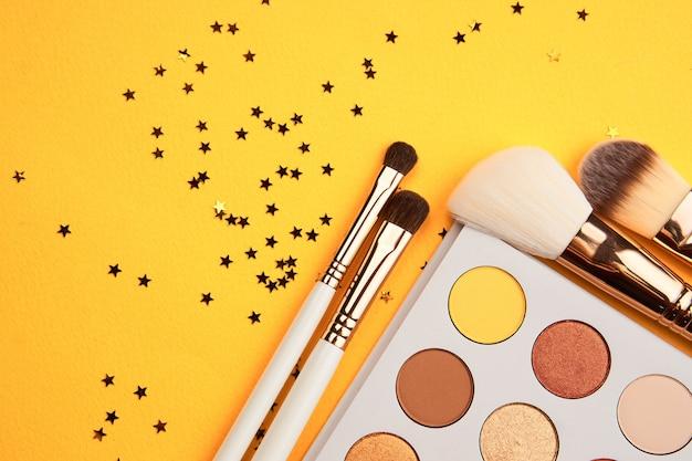 Ombretti e pennelli trucco su uno sfondo giallo vista dall'alto cosmetici professionali.