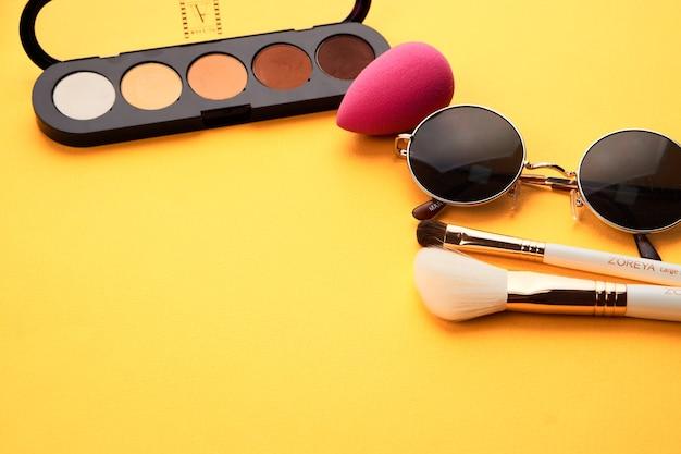 Ombretti su uno sfondo giallo cosmetici professionali pennelli trucco spugna morbida occhiali moda.