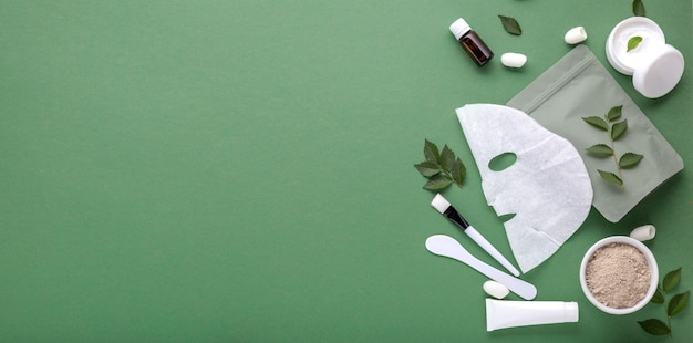 Maschera cosmetica in tessuto con set di spatola e pennello per maschera all'argilla, crema idratante in tubo, barattolo. trattamenti termali di bellezza per la cura della pelle del viso, cosmetologia banner web lungo copia spazio verde.