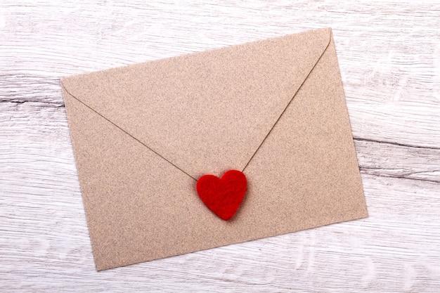 Cuore in tessuto su busta. lettera su superficie in legno. invia una lettera d'amore al tesoro. messaggio di solidarietà su carta.