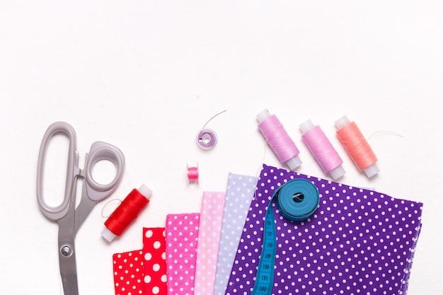 Tessuto, forbici e fili su uno sfondo bianco, accessori per cucire, copia spazio, vista dall'alto