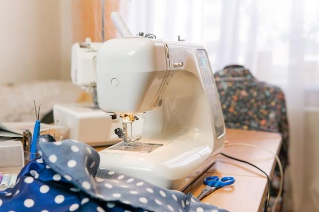 Tessuto, accessori per cucire e una macchina da cucire pronta all'uso su un tavolo in una stanza