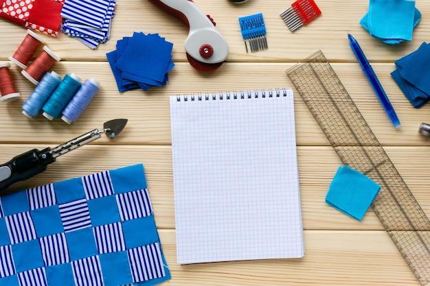 Tessuto e accessori per cucire con taccuino in bianco sulla tavola di legno